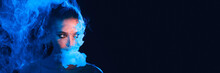 Mysterious Woman Smoking Electronic Cigarette In Neon Color Light