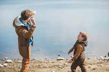 Father Teaching Little Son Throw Rocks In Water