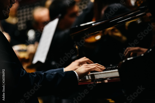 Foto Pianist playing a piece on a grand piano at a concert, seen from the side