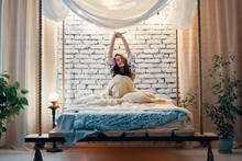Young Woman Stretching In Bed After Wake Up In Her Modern Apartment