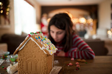 Gingerbread House Being Decorated By Little Girl During The Holidays
