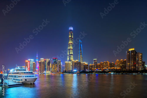 Montage in der Fensternische Shanghai Shanghai Downtown with a boat and Huangpu River, China. Financial district and business centers in smart city in Asia. Top view of skyscraper and high-rise buildings at night.