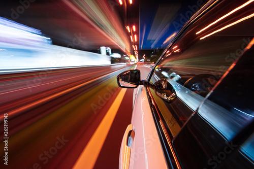 Foto auf Leinwand Violett rot Speeding car driving in a night city.