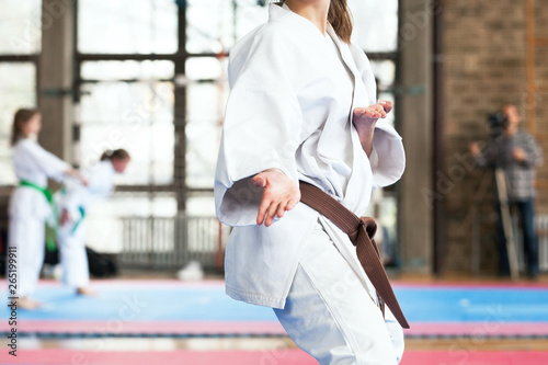 Female karate practitioner body position during competition. Martial arts.