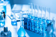 Different laboratory glassware with color liquid and with reflection, blue tone