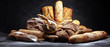 canvas print picture - Assortment of baked bread and bread rolls on rustic black bakery table background