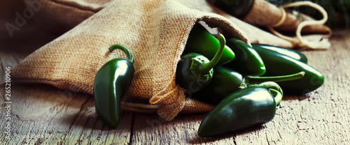 Fotomural Green jalapeno peppers, old wooden kitchen table background, selective focus