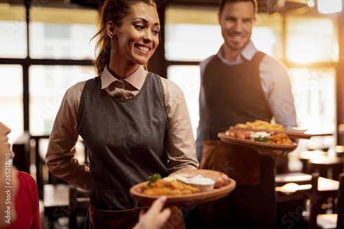 Fotografía  Happy waiters serving food to their guests in a restaurant.