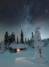 Light In Window Of Cabin Under Starry Sky In Snow