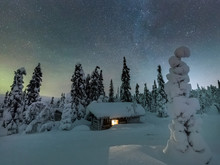 Light In Cabin Window Under Starry Night Sky In Snow