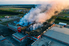Heavy Smoke In Burning Industrial Warehouse Or Storehouse Industrial Hangar From Burned Roof, Aerial View Of Fire Disaster