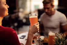Young Woman Enjoying In Glass Of Beer While Being In A Pub With Her Boyfriend.