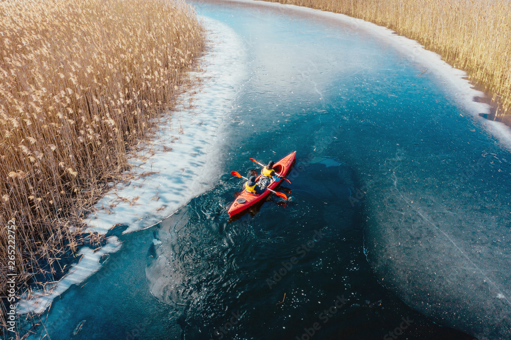 Fototapeta two athletic man floats on a red boat in river