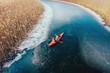Leinwandbild Motiv two athletic man floats on a red boat in river