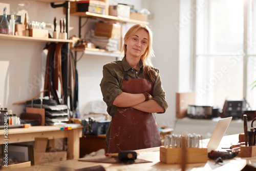 Photo Warm toned portrait of confident female artisan standing with arms crossed while