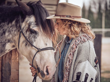 Side View Of Attractive Cowgirl With Closed Eyes Touching Head Of Dapple Gray Horse While Standing Near Stable On Blurred Background Of Ranch