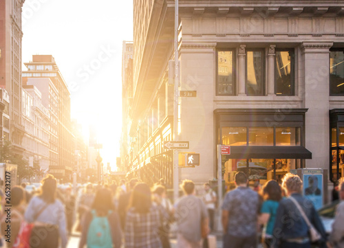 Photo Stands New York Crowd of anonymous people walking down the busy sidewalk on 23rd Street in Manhattan, New York City with bright light of sunset