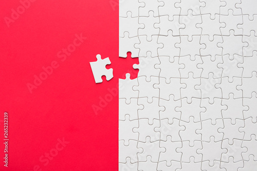 Fotografía  Red background made from white jigsaw puzzle pieces and place for your content