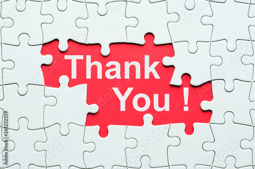 Photo Thank you word on red background reveal under white jigsaw puzzle
