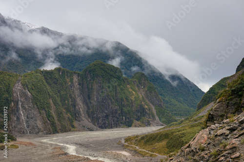 Leinwand Poster  Fox Glacier valley landscape with low clouds