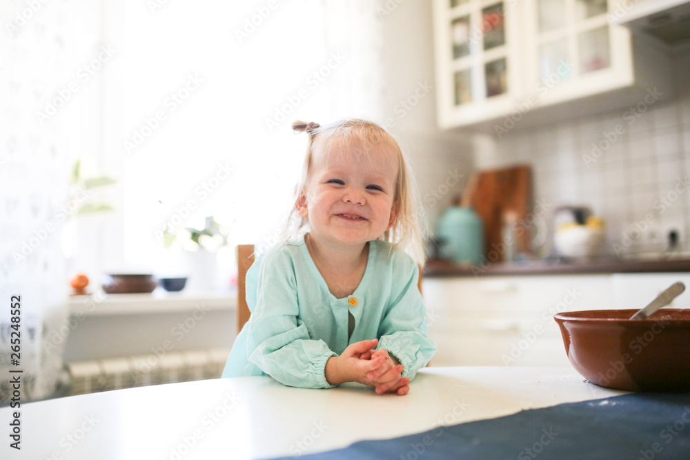 Fototapety, obrazy: Cute Toddler blonde girl sitting in the kitchen