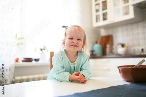 Valokuva  Cute Toddler blonde girl sitting in the kitchen