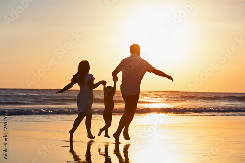 Fototapeta Happy family black silhouette on sun background. Father, mother, baby son run. Child jump with fun by water pool along sea surf on beach. Travel lifestyle, parents walking with kid on summer vacation. obraz na płótnie