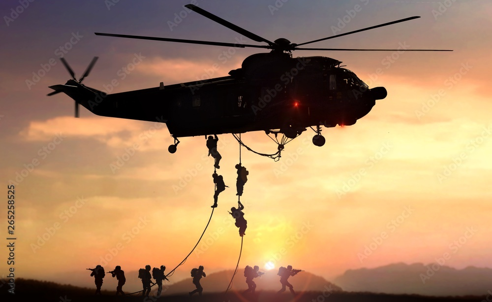 Fototapety, obrazy: Military commando helicopter drops in silhouette during sunset