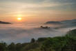 sunrise at Phu Huay Esan View Point, view of the hill around with sea of mist above Mekong river with soft red light in the sky background, Ban Muang, Sang Khom District, Nong Khai, Thailand.