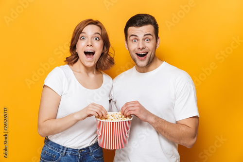 Excited beautiful couple wearing white t-shirts standing Wallpaper Mural