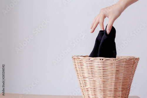 Fototapety, obrazy: Woman putting dirty socks in a laundry basket.copy space.