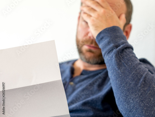 man reacting to bad news he receives in a letter selective focus Wallpaper Mural