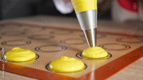 Photo Pastry chef is pouring dough from pastry bag on stencil silicone mat on the table