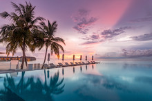 Idyllic Sunset Beach Scene, Infinity Pool In Luxury Resort, Tropical Landscape With Palm Trees And Sun Loungers And Closed Umbrellas. Luxury Summer Holiday And Beach Vacation Concept