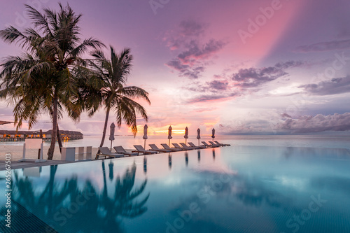 Obraz na plátne  Idyllic sunset beach scene, infinity pool in luxury resort, tropical landscape with palm trees and sun loungers and closed umbrellas