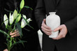 canvas print picture - Couple with mortuary urn and flowers at funeral