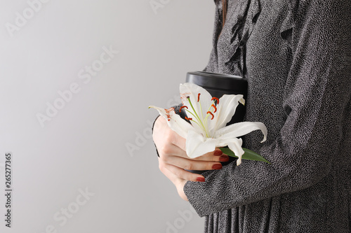 Woman with mortuary urn and lily flower on light background Fototapeta