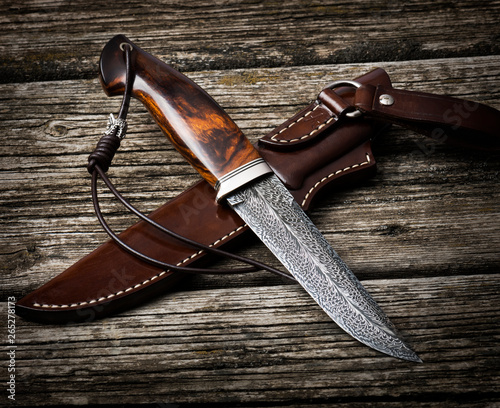 Photo  hunting knife handmade on a brown wooden background