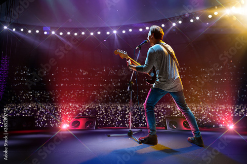 Rock star celebrity on the main stage big music festival. Aroun full stadium of spectators. fans are holding flashlights - 265280750