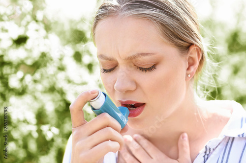 Photo Woman with inhaler having asthma attack outdoors