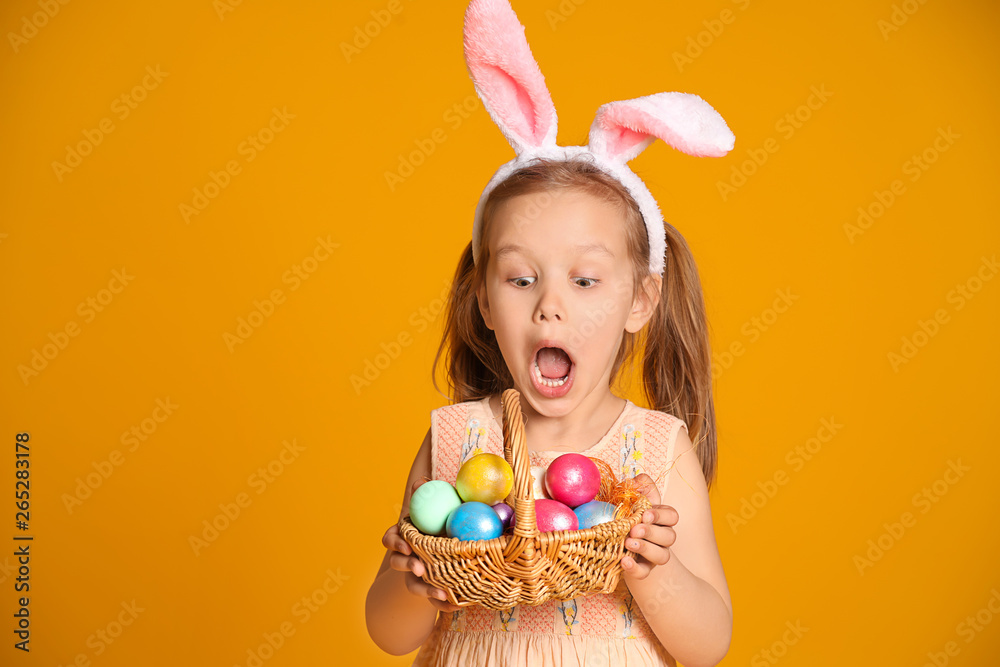 Fototapety, obrazy: Surprised little girl with basket of Easter eggs and bunny ears on color background