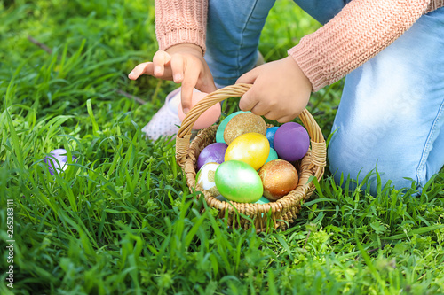 Little girl gathering Easter eggs in park, closeup Wallpaper Mural
