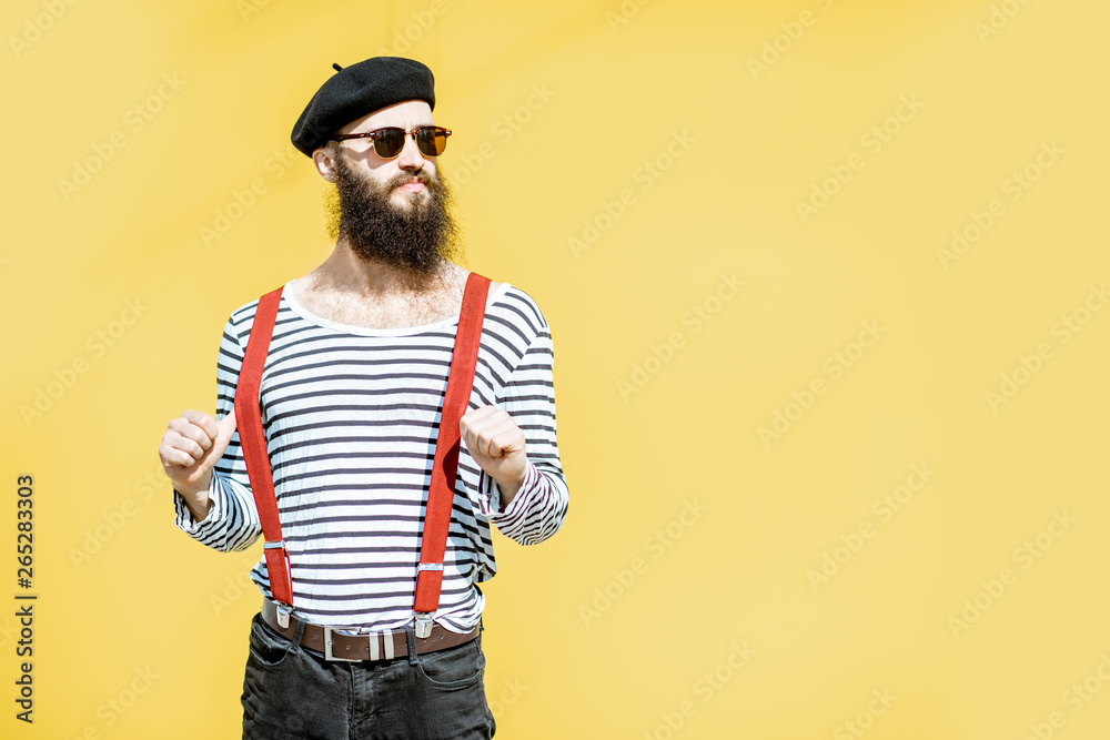 Fototapeta Portrait of a stylish bearded man dressed in striped shirt, suspenders and hat on the yellow background outdoors
