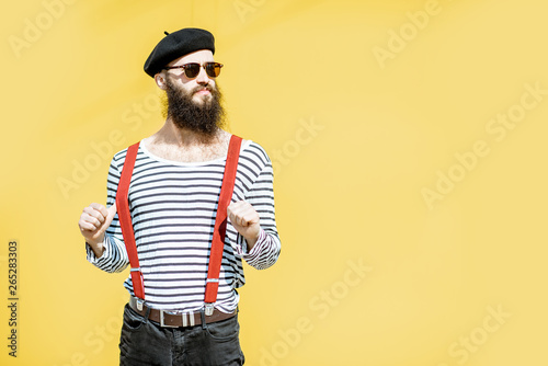 Fotografia, Obraz  Portrait of a stylish bearded man dressed in striped shirt, suspenders and hat o