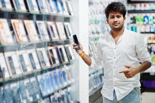 In de dag Apotheek Indian man customer buyer at mobile phone store choose his new smartphone. South asian peoples and technologies concept. Cellphone shop.