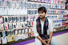 Indian Man Customer Buyer At Mobile Phone Store Sitting On Chair. South Asian Peoples And Technologies Concept. Cellphone Shop.