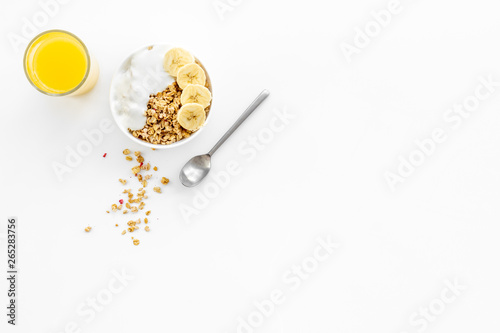 Fototapeta Bright breakfast with granola and orange juice on white background top view mock
