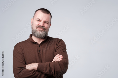 Foto  Angry, pissed off mature man with arms crossed folded.