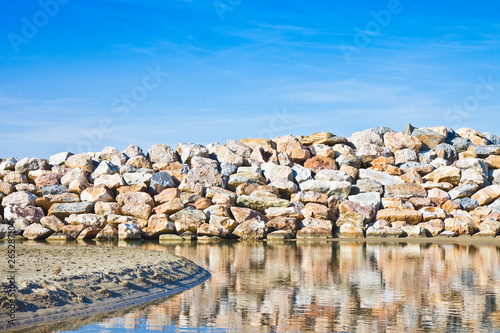 Retaining breakwater wall built with stone boulders Canvas Print