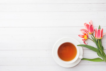 Cup of tea and flowers tulips on white table with copy space. Flat lay, top view.